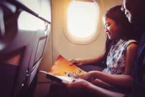 Young girl reading a book on an airplane while traveling