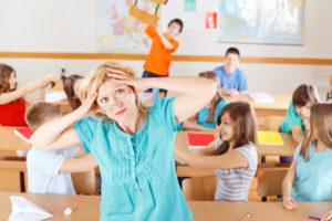 teacher pulling hair out as classroom devolves into disorder behind her