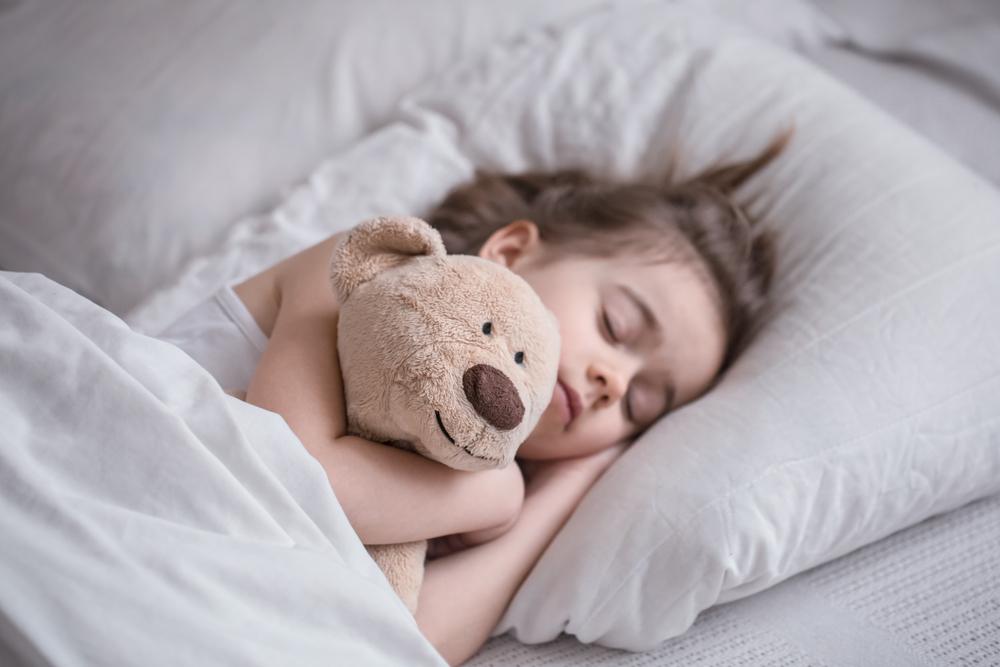 little girl sleeping with teddy bear